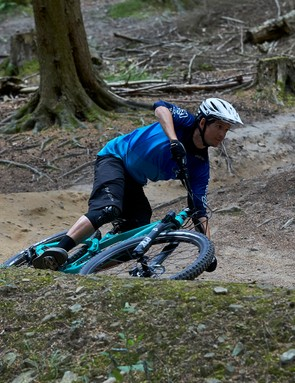 male cyclist riding gloss pitch green full suspension mountain bike on dirt track