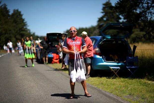 A soigneur waits to hand out musettes to the team riders