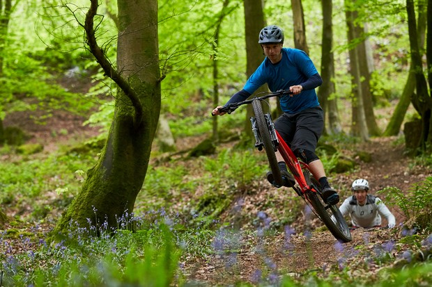male cyclist riding red mountain bike through woods