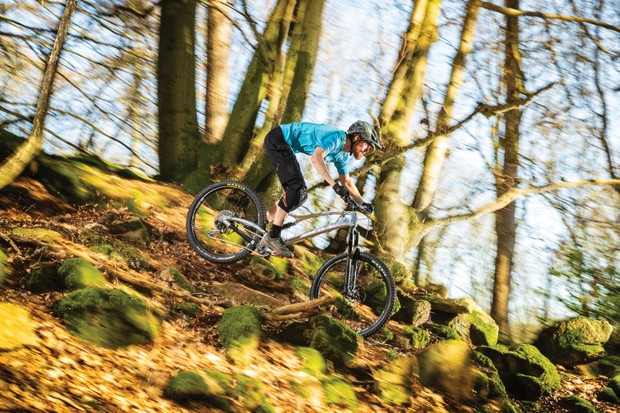 Cyclist riding silver full-suspension bike down hill in woods