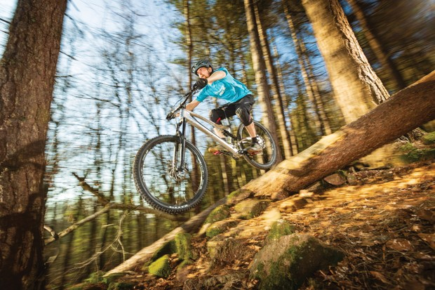 Cyclist riding silver full-suspension bike downhill in woods