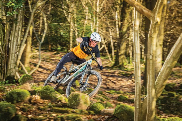 Cyclist riding full suspension mountain bike in woods