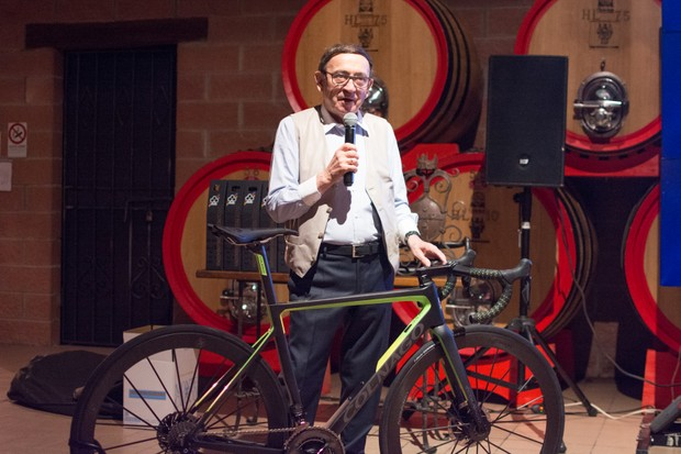 Man with microphone standing behind high end road bike
