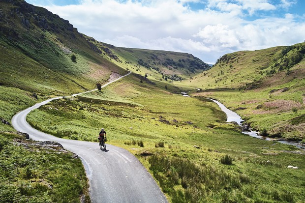 Cyclist riding through Cambrian Mountains in Wales