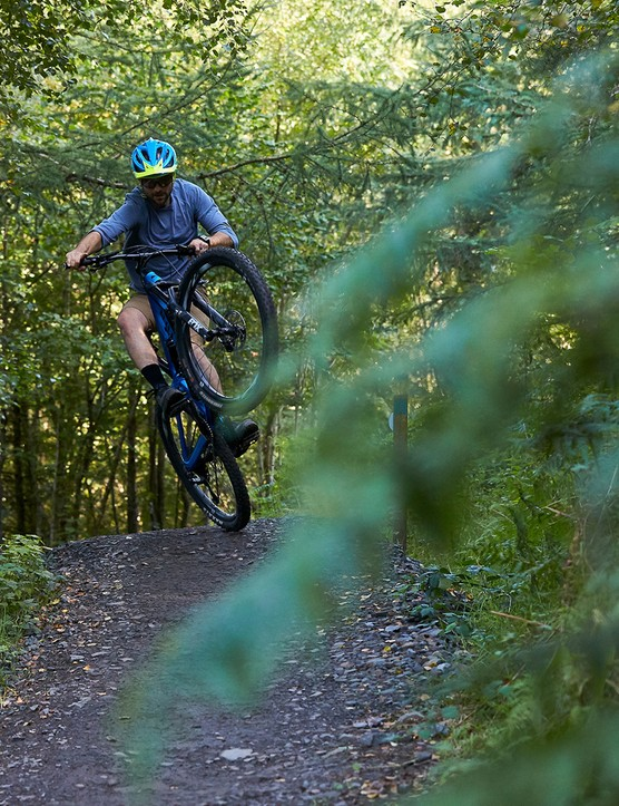 male cyclist riding blue full suspension mountain bike through woods