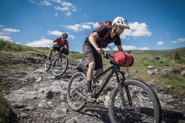 Cyclists riding mountain bikes over rocky path