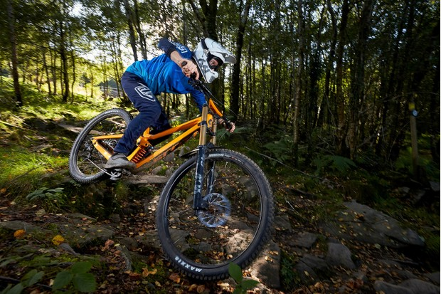 male cyclist riding orange full suspension mountain bike in woods