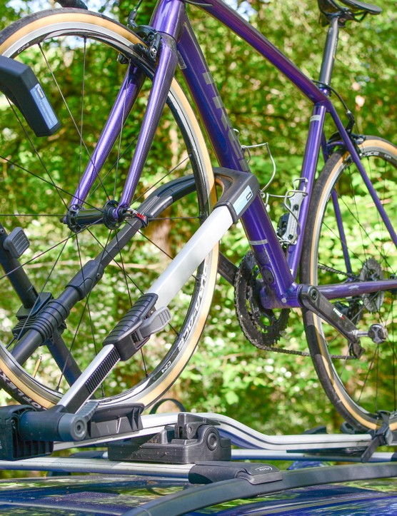 Purple bike on roof-mounted bike rack, on car