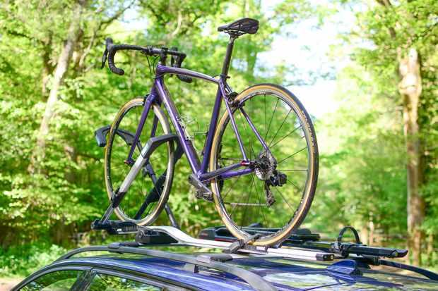 Purple bike on roof-mounted bike rack, on car