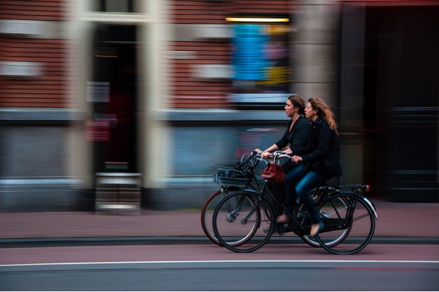 Two cyclists rding through street