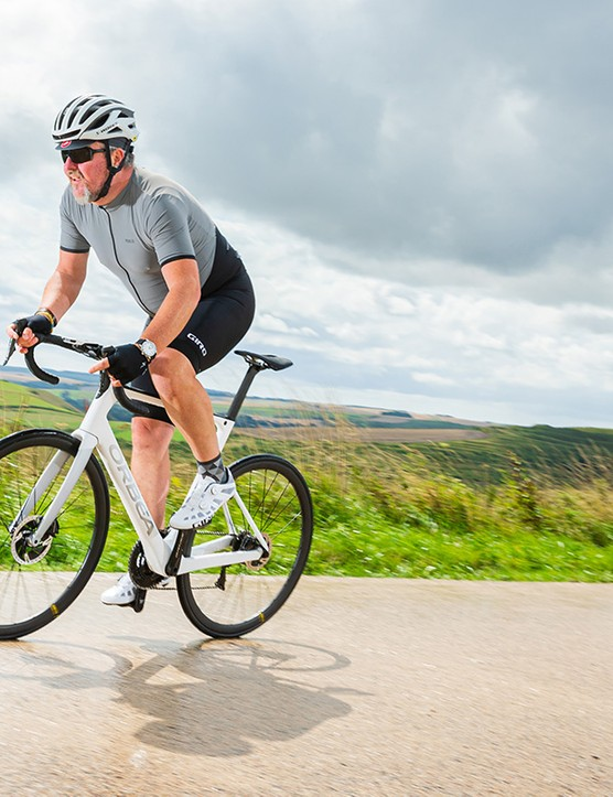 male cyclist riding white orbea road bike