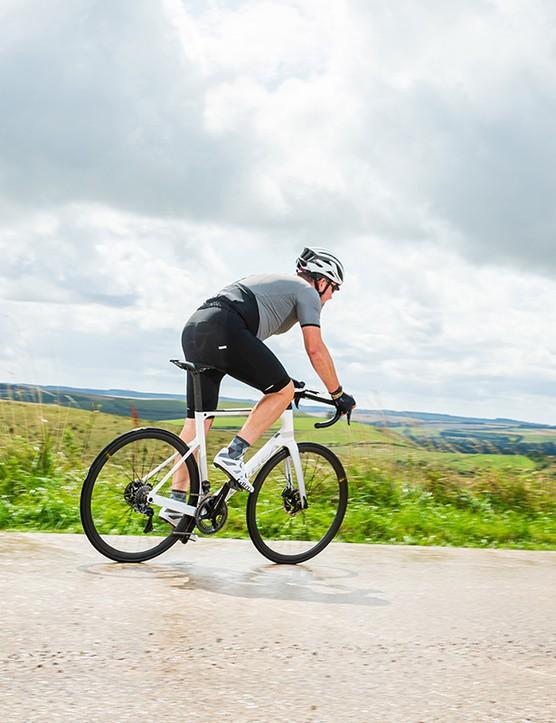 male cyclist riding white orbea road bike