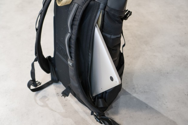Laptop emerging from side compartment of rucksack