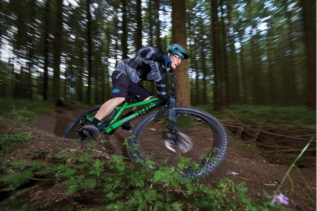 male cyclist riding green hardtail mountain bike in woods