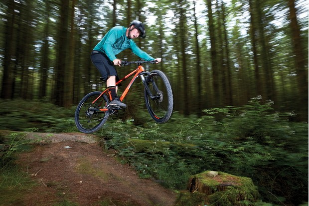 male cyclist riding orange hardtail mountain bike in woods