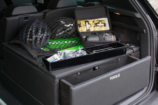 The washing machine and bike washer are concealed beneath the helmet storage net. A tool drawer opens outwards