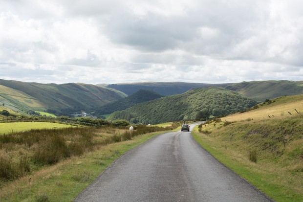 Car with bikes on roof in hilly Welsh landscape