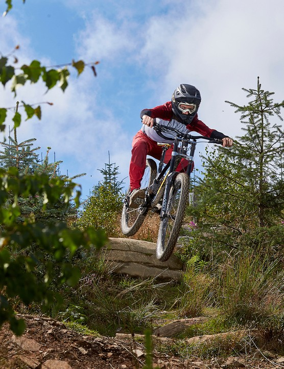 male cyclist wearing red riding black full suspension mountain bike on dirt track