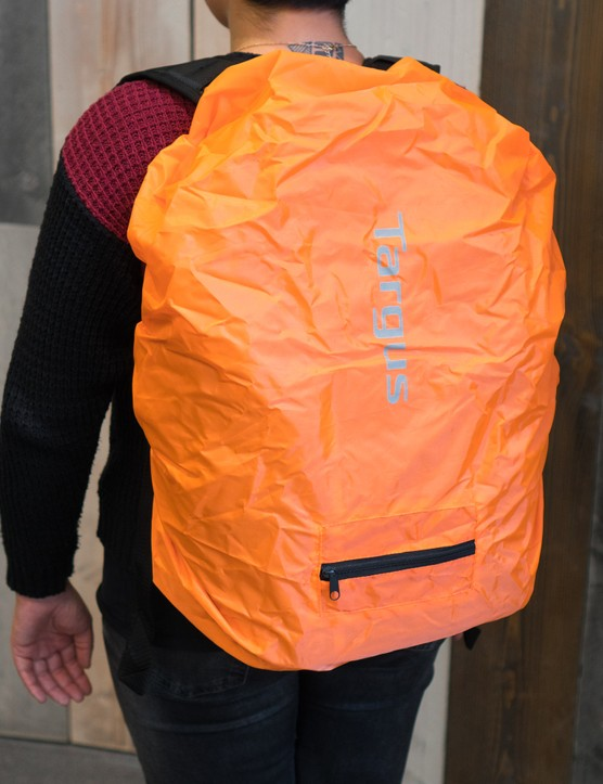 Woman wearing rucksack with orange rain cover.