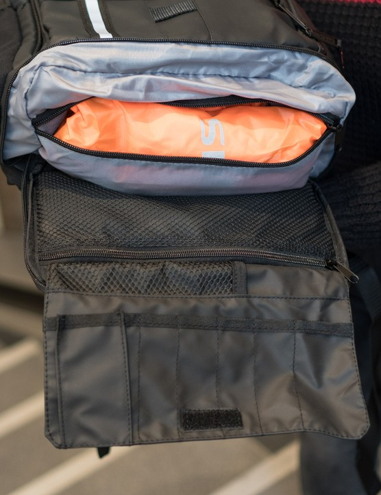 Open lower section of cycling rucksack showing rolled rain cover and tool roll.