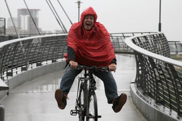 Man in rain on bike having fun