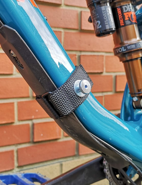 Large metal pin mounted to strap on bike frame