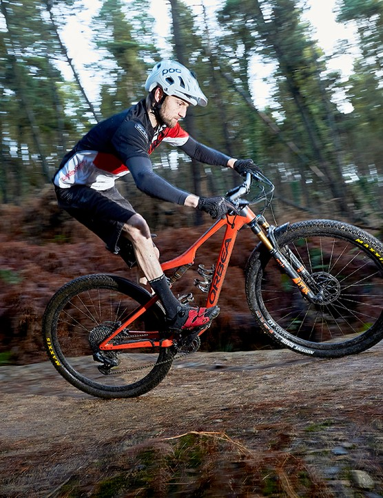 Male cyclist riding red full suspension mountain bike