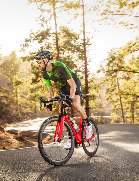 Male cyclist in green top riding the Trek Madone SL6 Disc