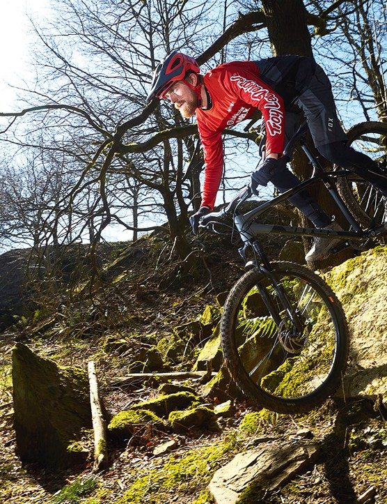 Male cyclist riding the Vitus Sentier 29 hardtail mountain bike over rocky terrain