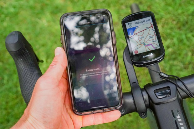 Garmin Edge 830 GPS bike computer with on-device mapping connected to an iPhone with Garmin Connect app showing a selected route