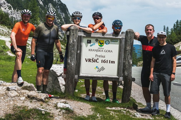 Cyclist find time for a photo shot at the summit of the Vřsič Pass in the Julian Alps of Slovenia
