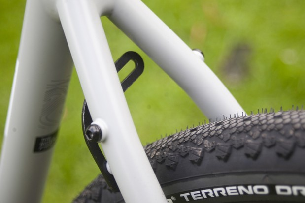 The rear seat stay bridge on the Cairn E-Adventure V2 has been replace with a single sided bolt on mudguard mount