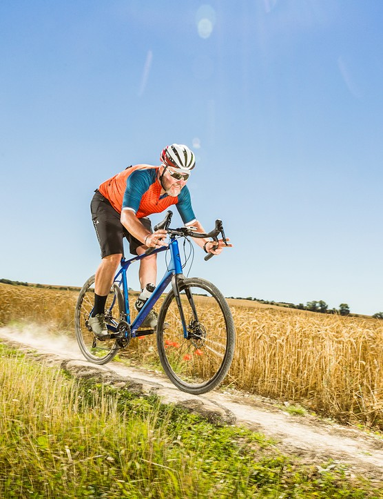 Male cyclist in red top riding the Merida Silex 400 gravel bike