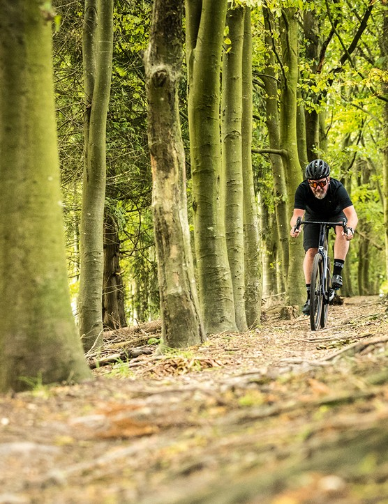 Male cyclist riding the Ridley Kanzo Fast GRX Di2 Classified gravel bike through woodland