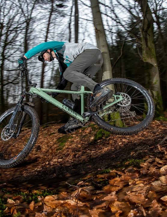 Male cyclist riding the Canyon Stoic 4 hardtail mountain bike through woodland