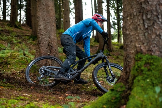 Male cyclist in blue top riding the Evil Offering GX Hydra full suspension mountain bike through woodland