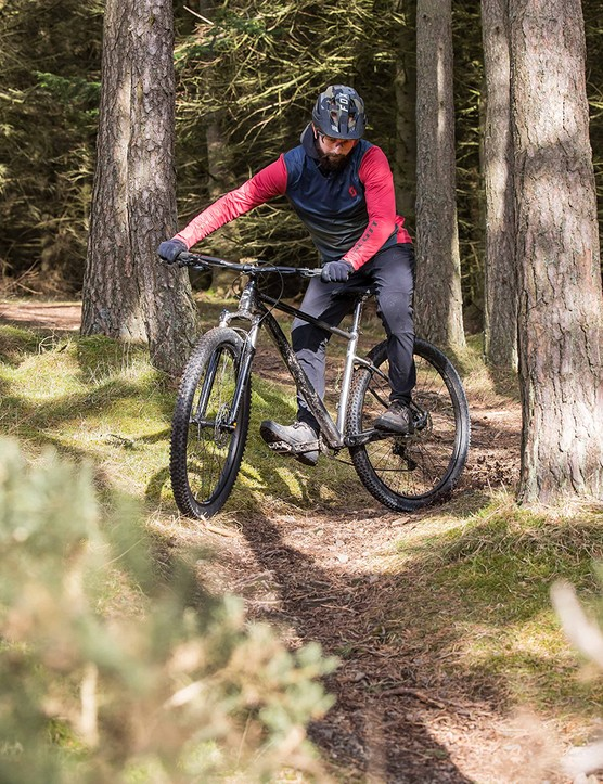 Male cyclist in blue and red top riding the Cannondale Trail SE4 hardtail mountain bike through woodland
