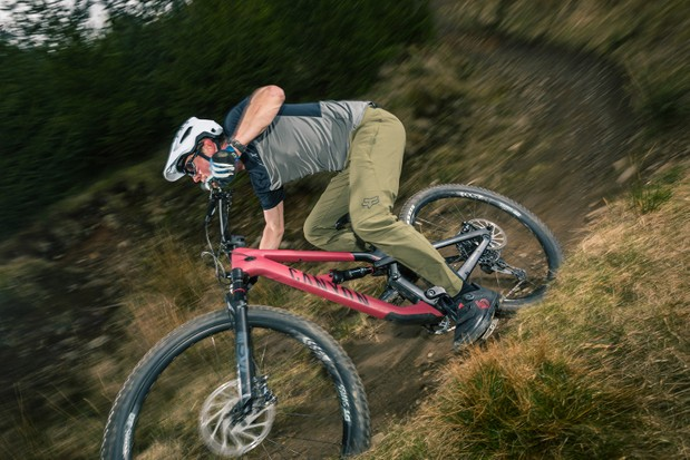 Male cyclist in grey and blue top riding the Canyon Spectral 29 CF 7