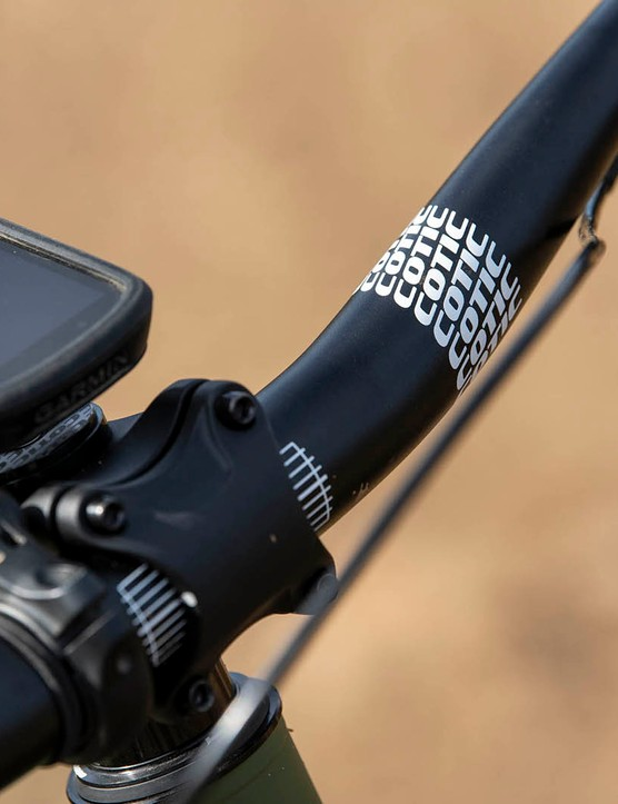 The Cotic RocketMAX Gen3 Silver SLX full suspension mountain bike is equipped with own brabded bar and stem
