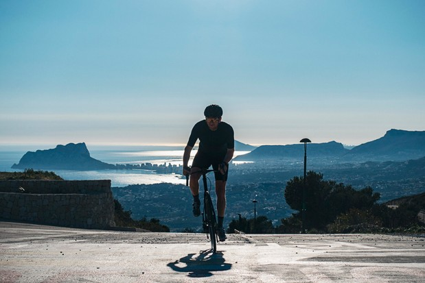 Cyclist climbing with view of Calpe behind