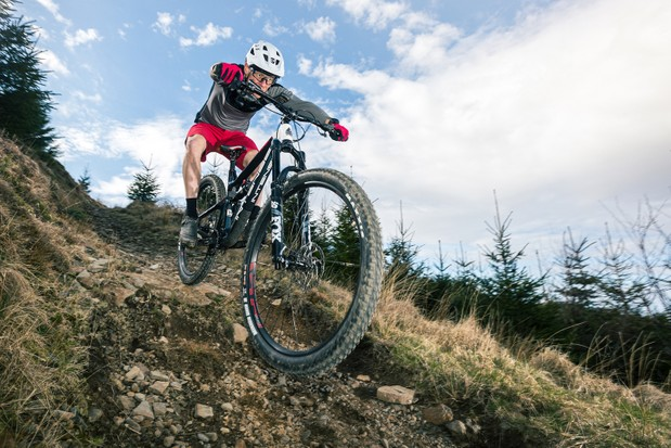 Male cyclist in grey top riding the Intense Primer 29 Expert full suspension mountain bike downhill