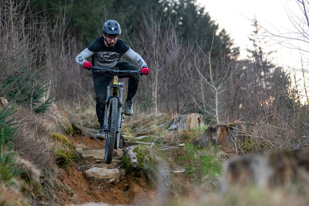 Cyclist in grey top riding the Kona Process 153 DL 29 full suspension mountain bike