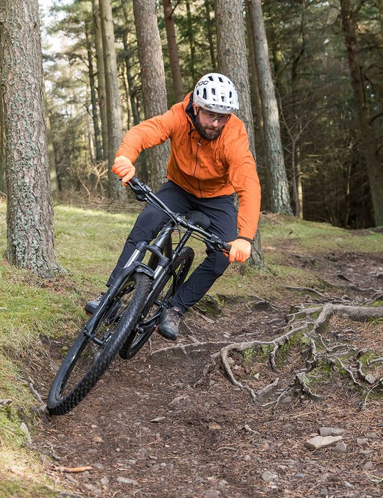Male cyclist in orange top riding the Specialized Rockhopper Comp hardtail mountain bike through woodland