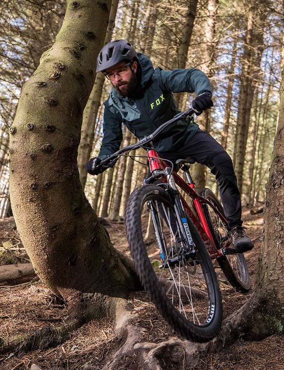 Male cyclist in blue top riding the Vitus Nucleus 29 VRS hardtail mountain bike through woodland