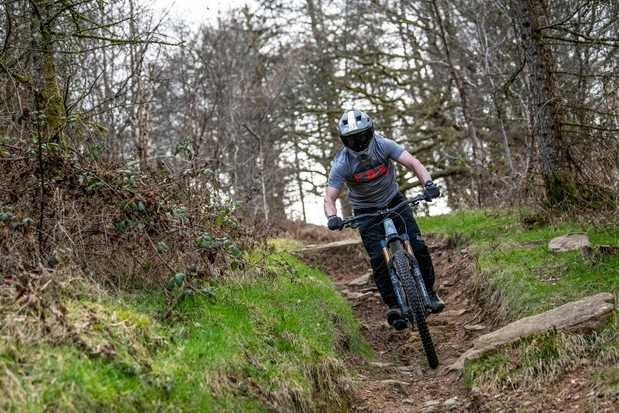 Cyclist in grey top riding the Vitus Sommet CRX 29 full suspension mountain bike