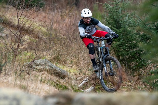 Cyclist in grey top riding the YT Capra Shred 27.5 over rough ground
