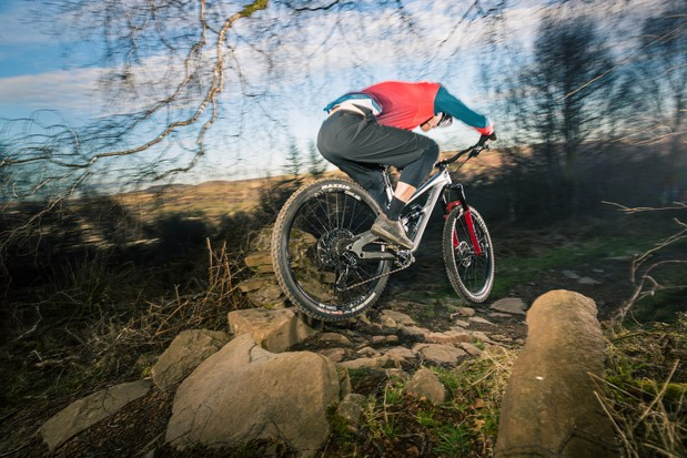 Male cyclist in red top riding the YT Jeffsy Blaze full suspension mountain bike over rocky ground