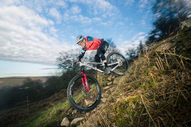 Cyclist in red top riding the YT Jeffsy Blaze full suspension mountain bike downhill over rocky ground