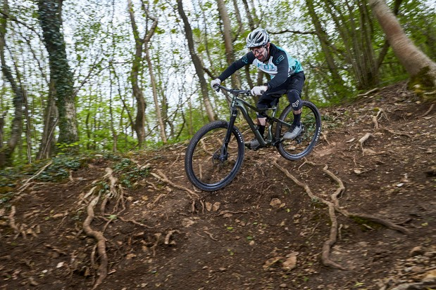 Cycist in blue top riding the Cannondale Scalpel SE LTD Lefty full suspension mountain bike