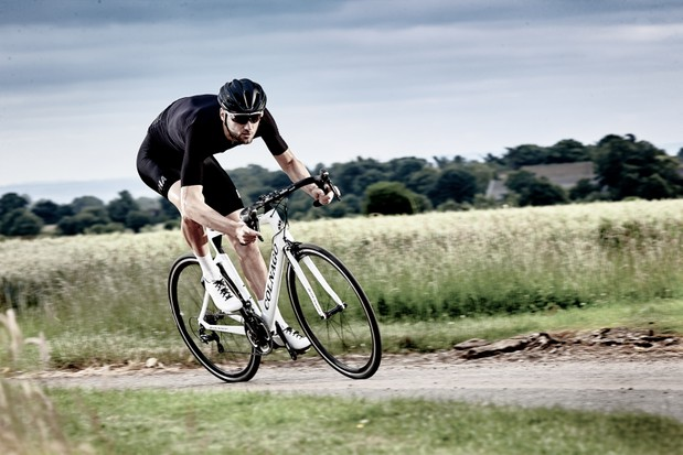 Road cyclist riding fast in the drops